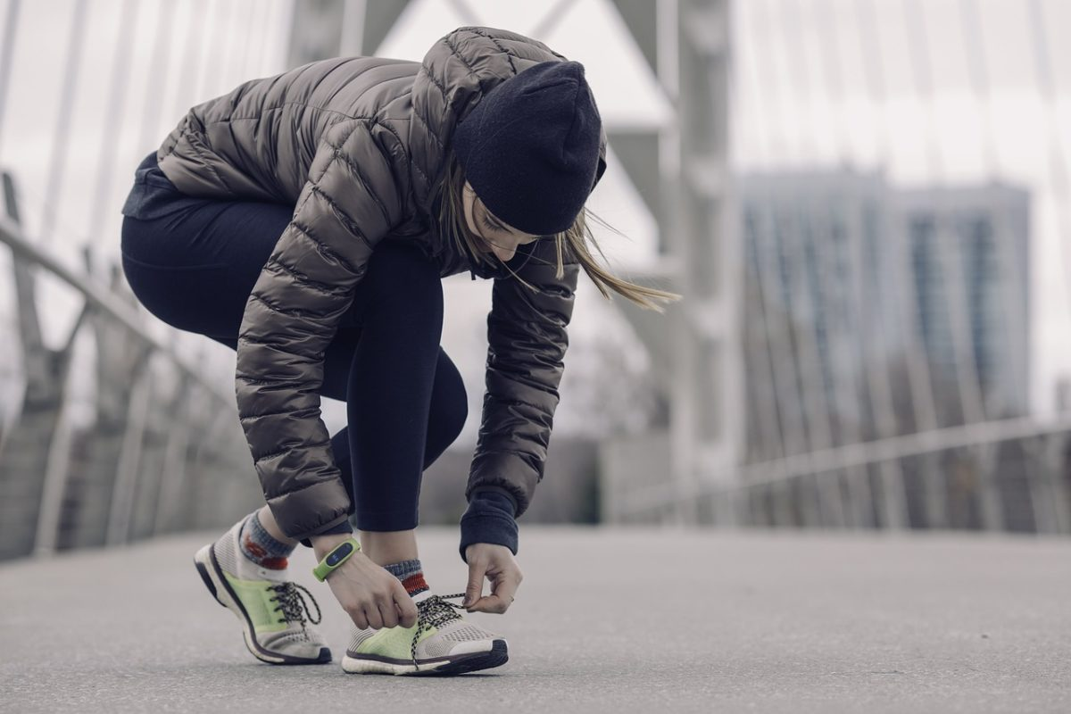 girl bends to tie shoes in winter